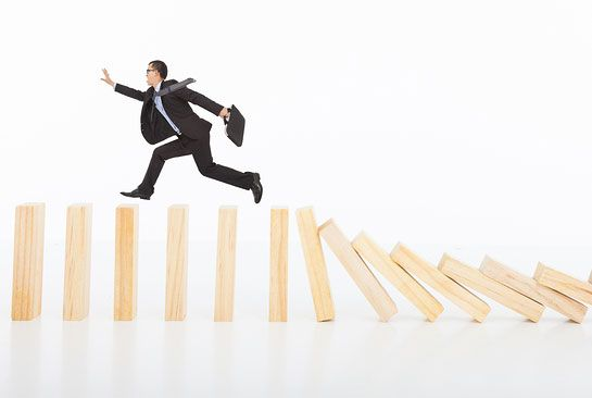 businessman running and catching on toppling dominoes over white